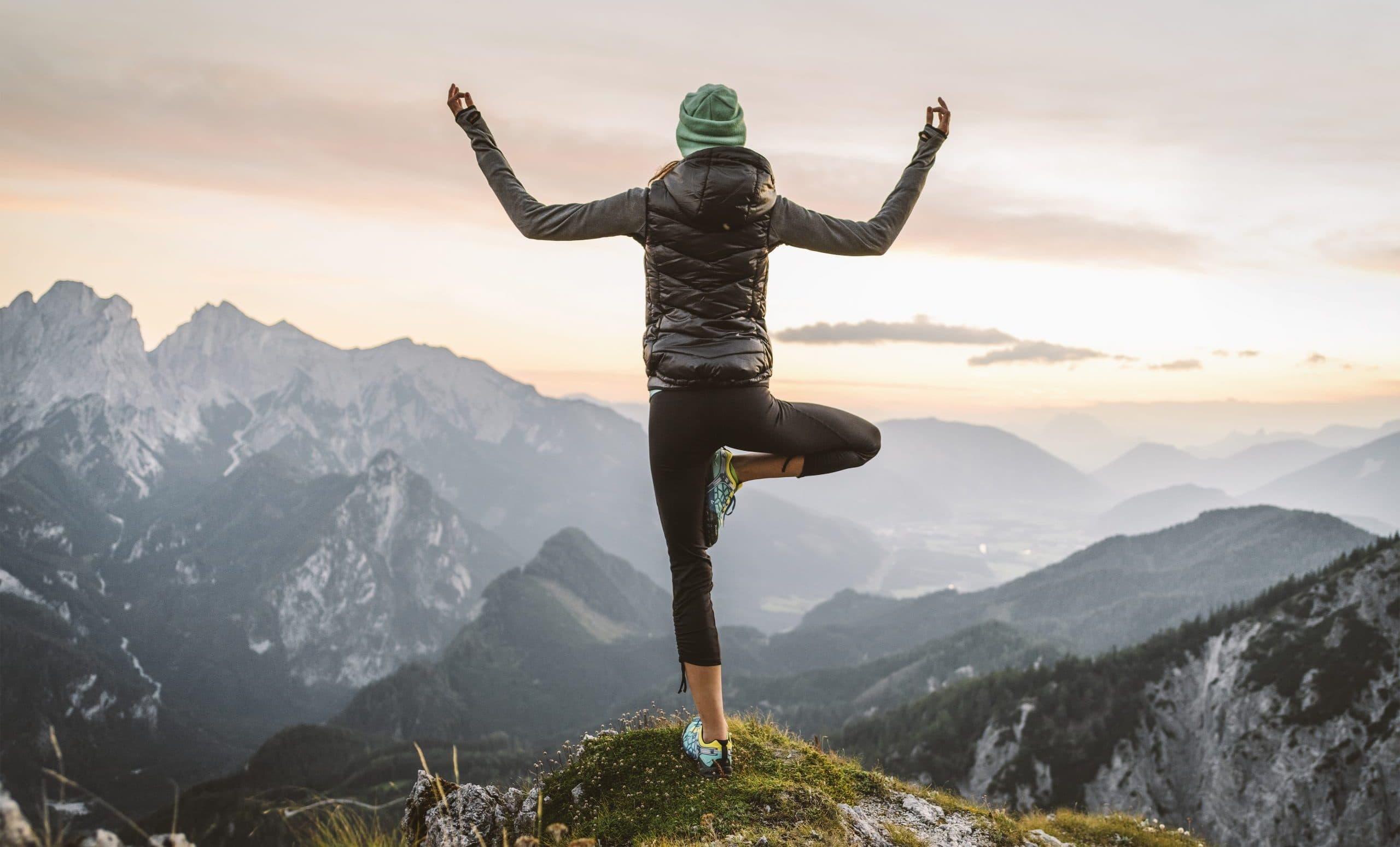 Frau macht Yoga am Berg